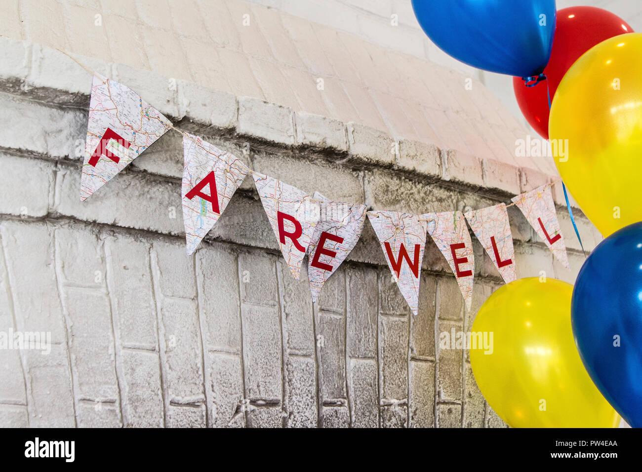 Texto de despedida en buntings por coloridos globos de helio contra la pared colgante Imagen De Stock