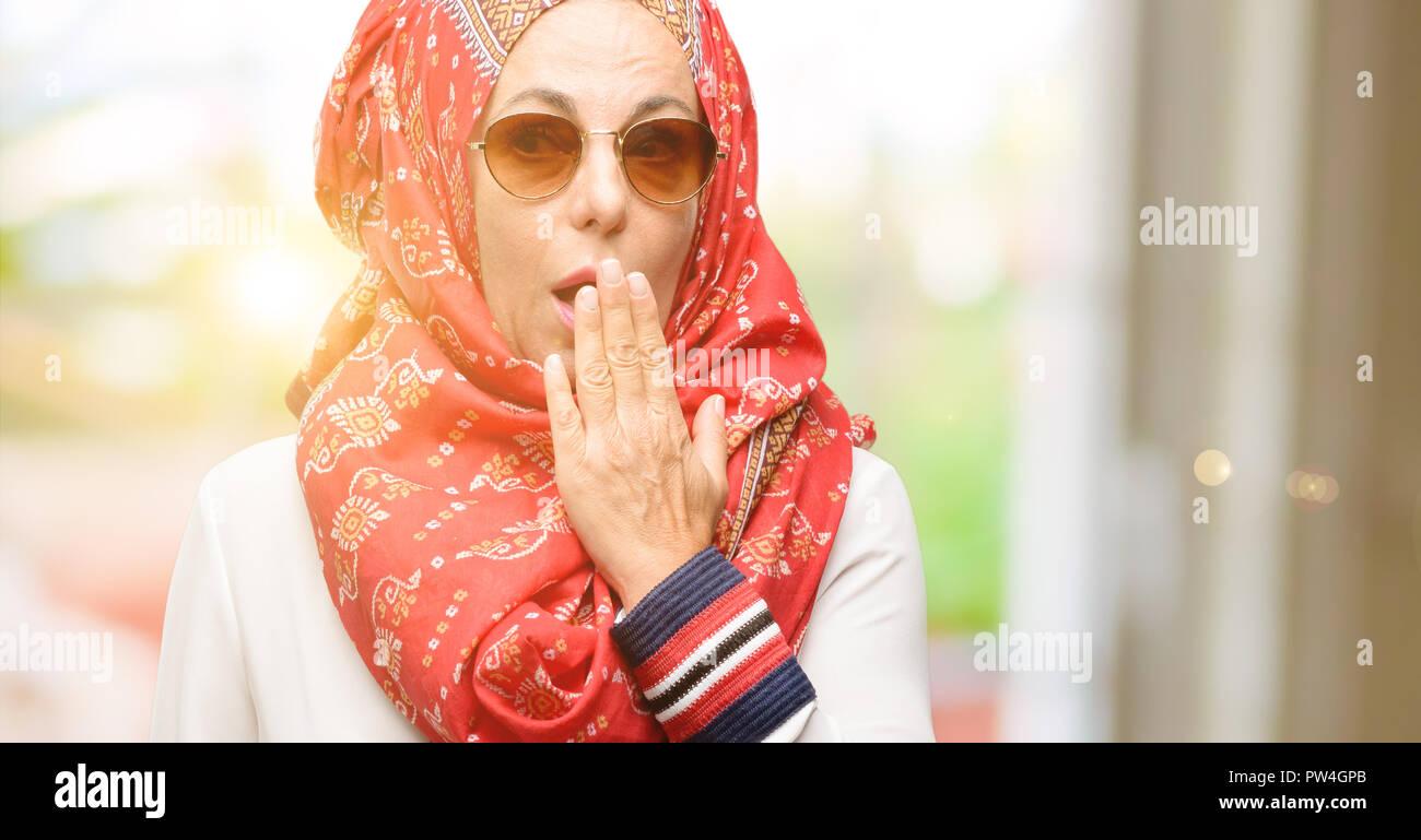 Edad media los árabes musulmanes mujer vistiendo el hijab cubre boca en estado de shock, parece tímido, expresando el silencio y confundir los conceptos, asustada Foto de stock