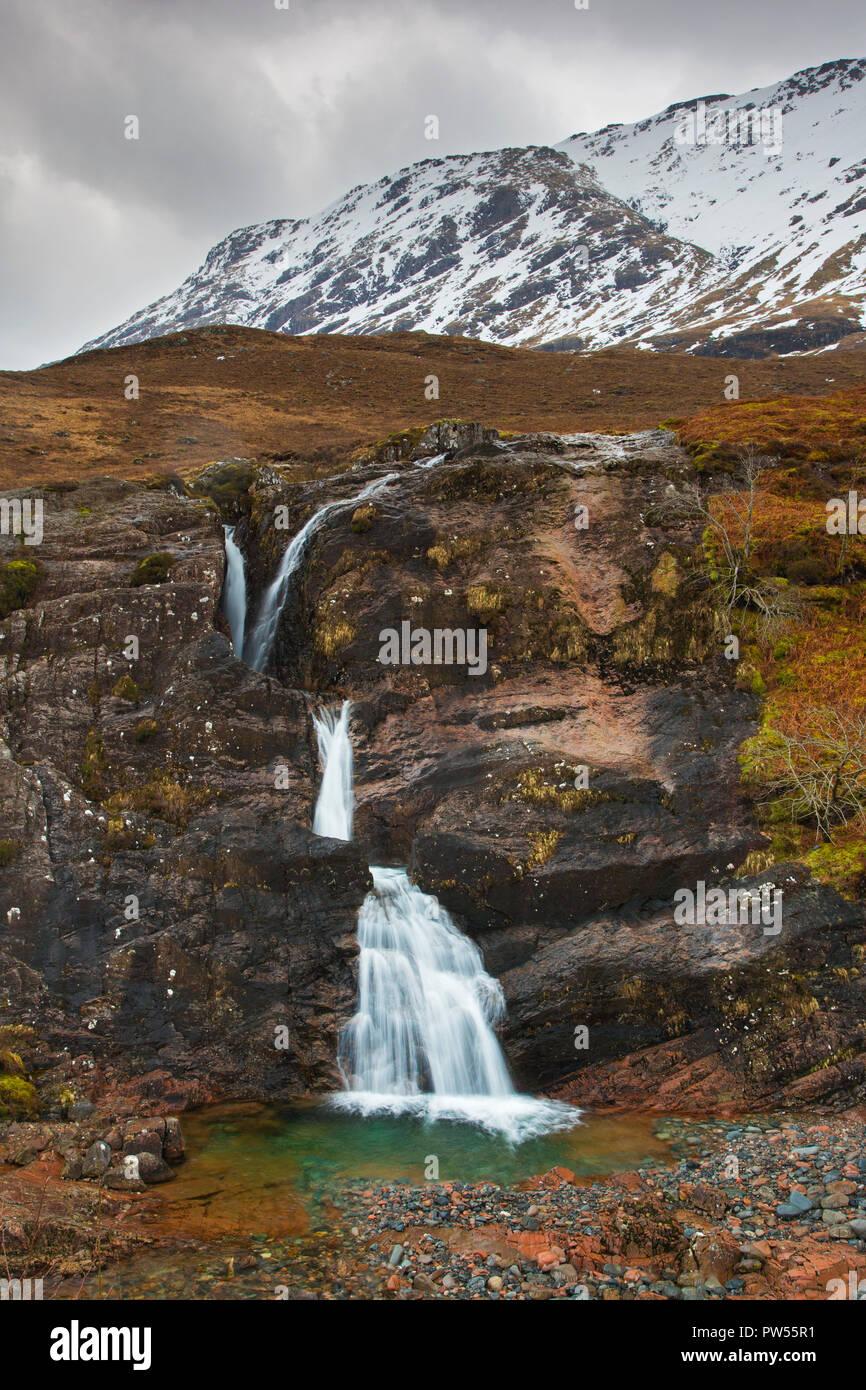Reunión de tres aguas, cascada al pie de las tres hermanas de Glen Coe / Glencoe en invierno, Highlands, Escocia, Gran Bretaña Foto de stock