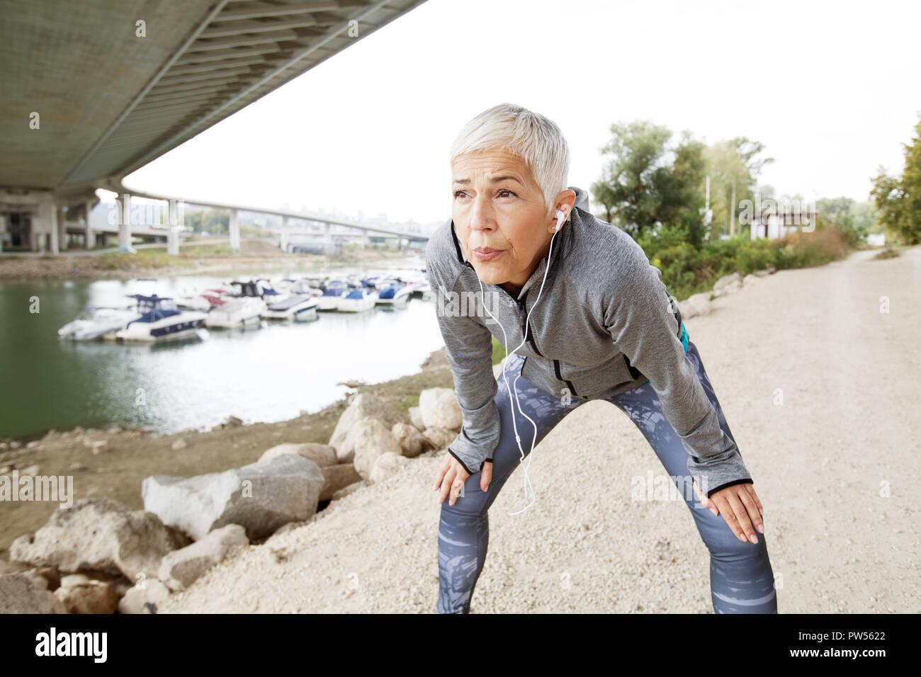 Activa ejecutando Senior Mujer descansando después de correr escuchando música con el smartphone en la orilla del río , entrenar al aire libre. Foto de stock