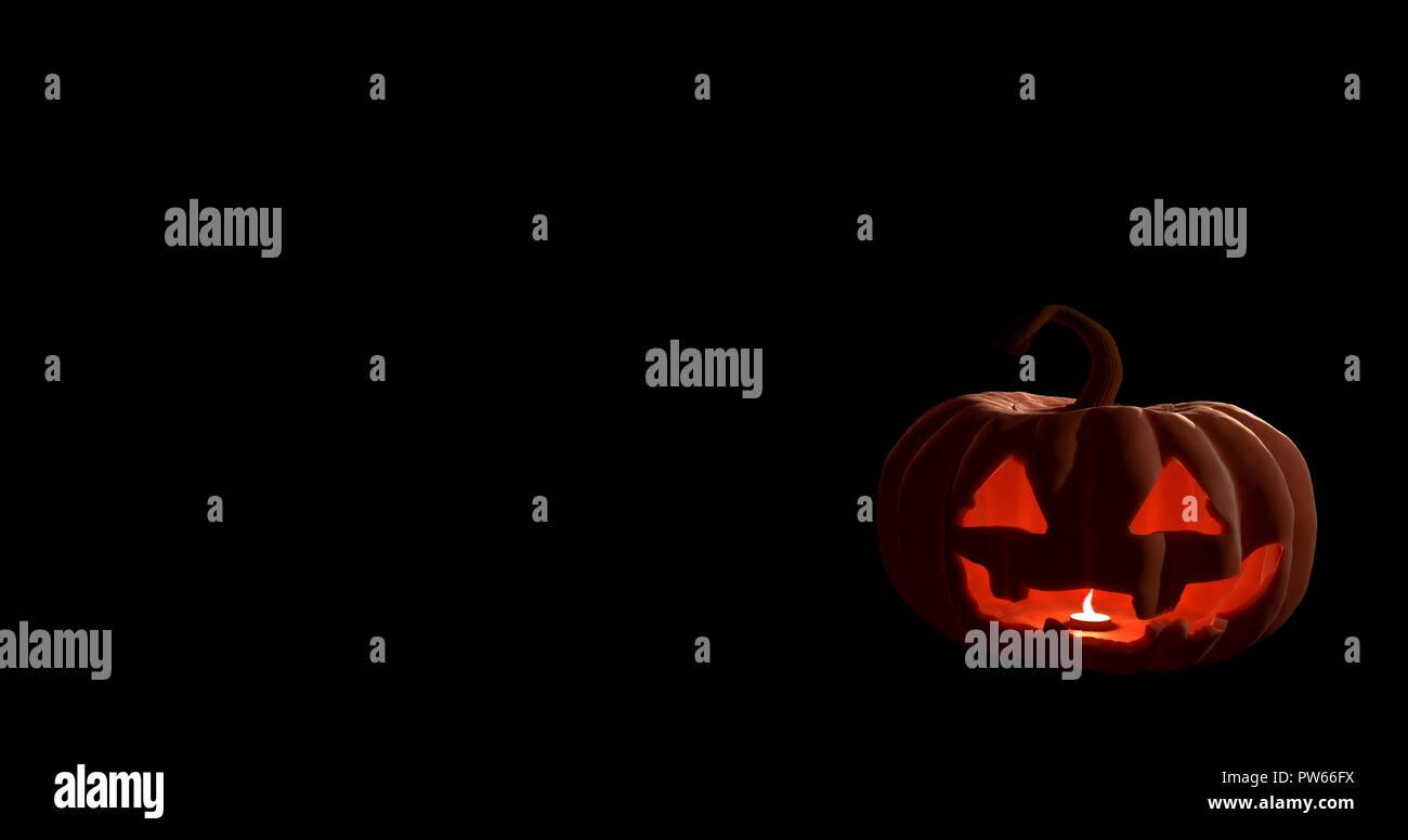 Halloween calabaza con cara de miedo sobre fondo negro. Foto de stock
