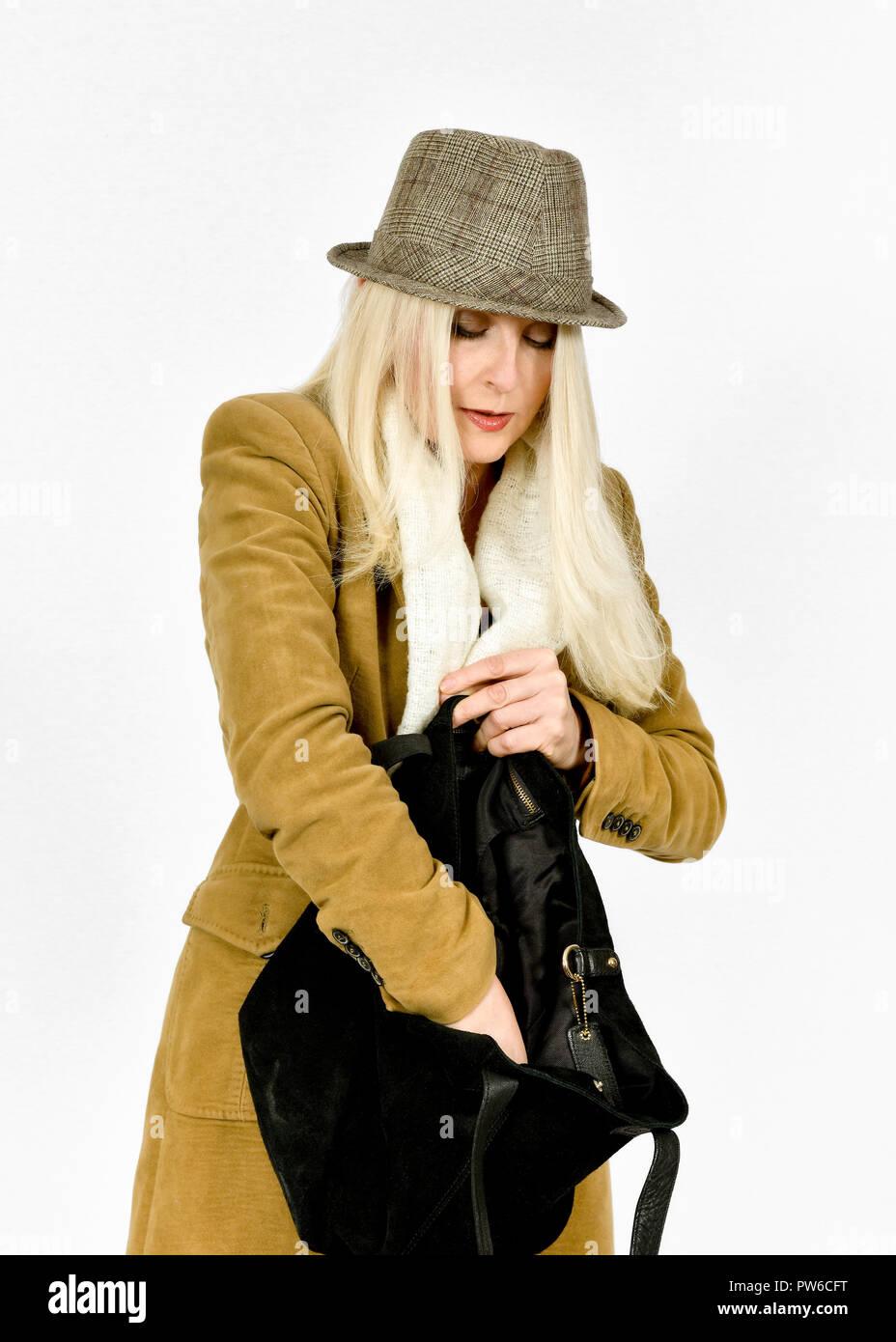 Atractiva mujer rubia en ropa de invierno buscando algo en su bolso Imagen De Stock