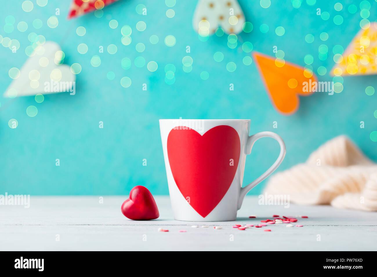 Copa romántica con chocolate dulces en forma de corazón. Fondo azul con corazones de papel guirnalda Foto de stock