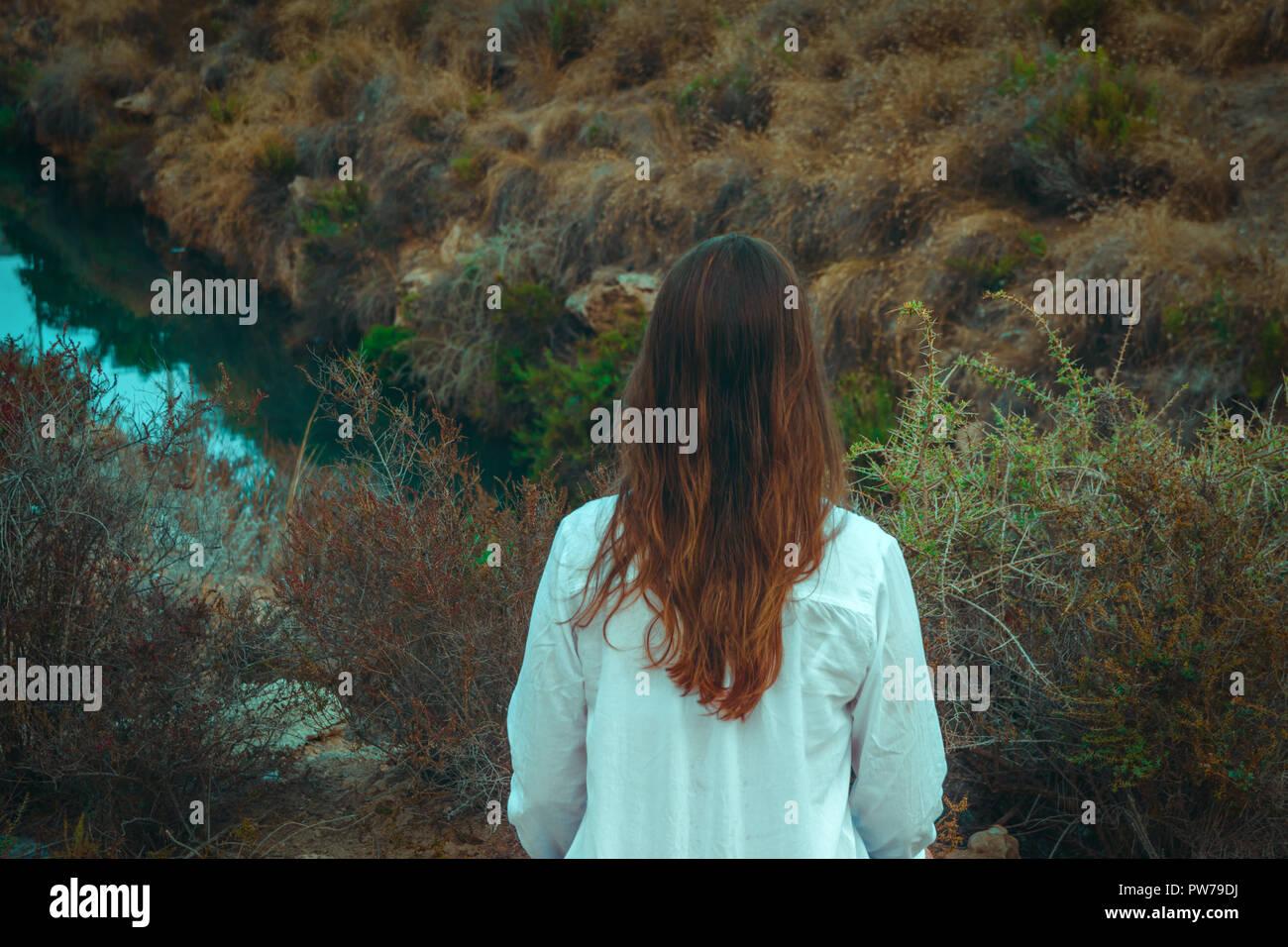 f43d74ead Joven mujer caucásica con largo cabello castaño en camisa de lino blanco  permanente del río mira