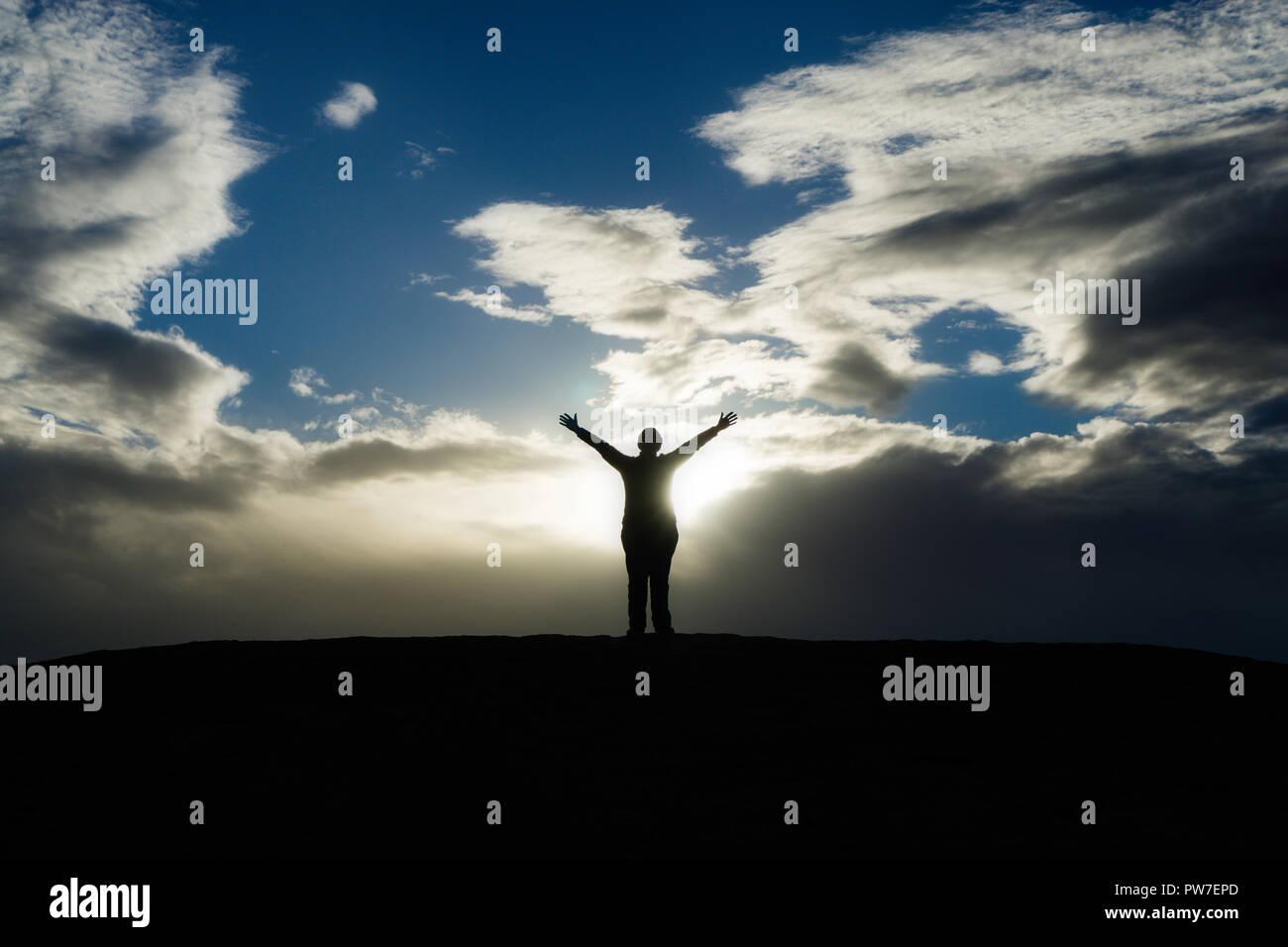 Silueta de persona de pie con los brazos como Sun rompe a través de las nubes. Imagen De Stock