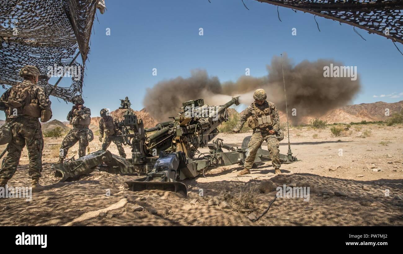 Infantes de Marina de los Estados Unidos asignado al 11º Regimiento de la Infantería de Marina, la primera división de infantería de marina, disparar un obús M777 durante el curso de Instructor de armas y tácticas (WTI) 1-18 en la antena de la montaña de Chocolate Tiro, California, 26 de septiembre de 2017. El WTI es un evento de capacitación de siete semanas organizado por la Aviación Marina armas y tácticas de escuadrón MAWTS Uno (cuadro 1), haciendo hincapié en la integración operacional de las seis funciones de aviación del Cuerpo de Infantería de Marina en apoyo de una masa de aire marino Task Force. Foto de stock