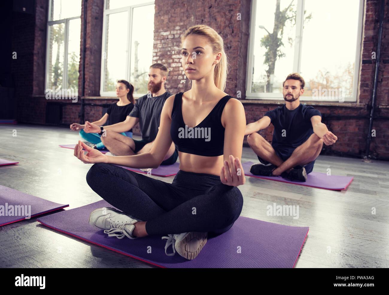 La meditación del yoga de jóvenes en lotus plantear en el gimnasio Imagen De Stock