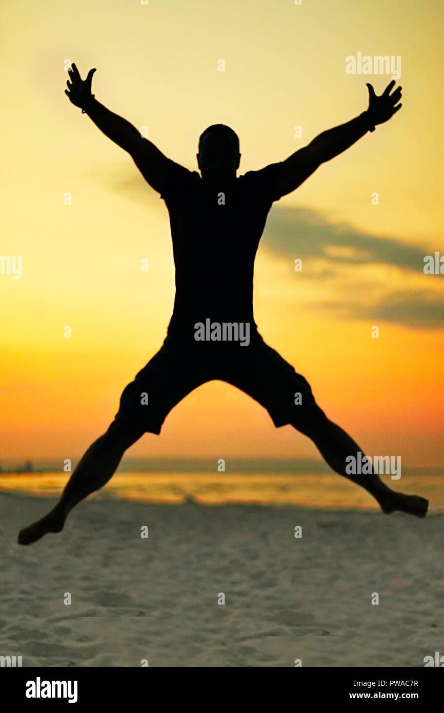 Silueta de un hombre negro saltando en el aire en forma de X. En el fondo es un brillante cielo nocturno con hermosos colores amarillos y naranjas. Imagen De Stock