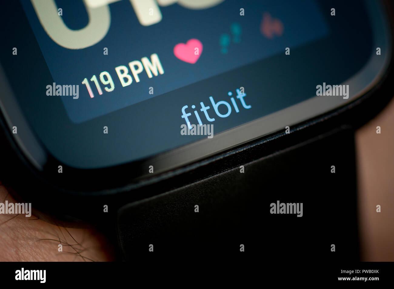 Un hombre comprueba su actividad Versa Fitbit tracker incluido monitor de ritmo cardíaco usando BPM unidades durante un ejercicio de entrenamiento. Imagen De Stock