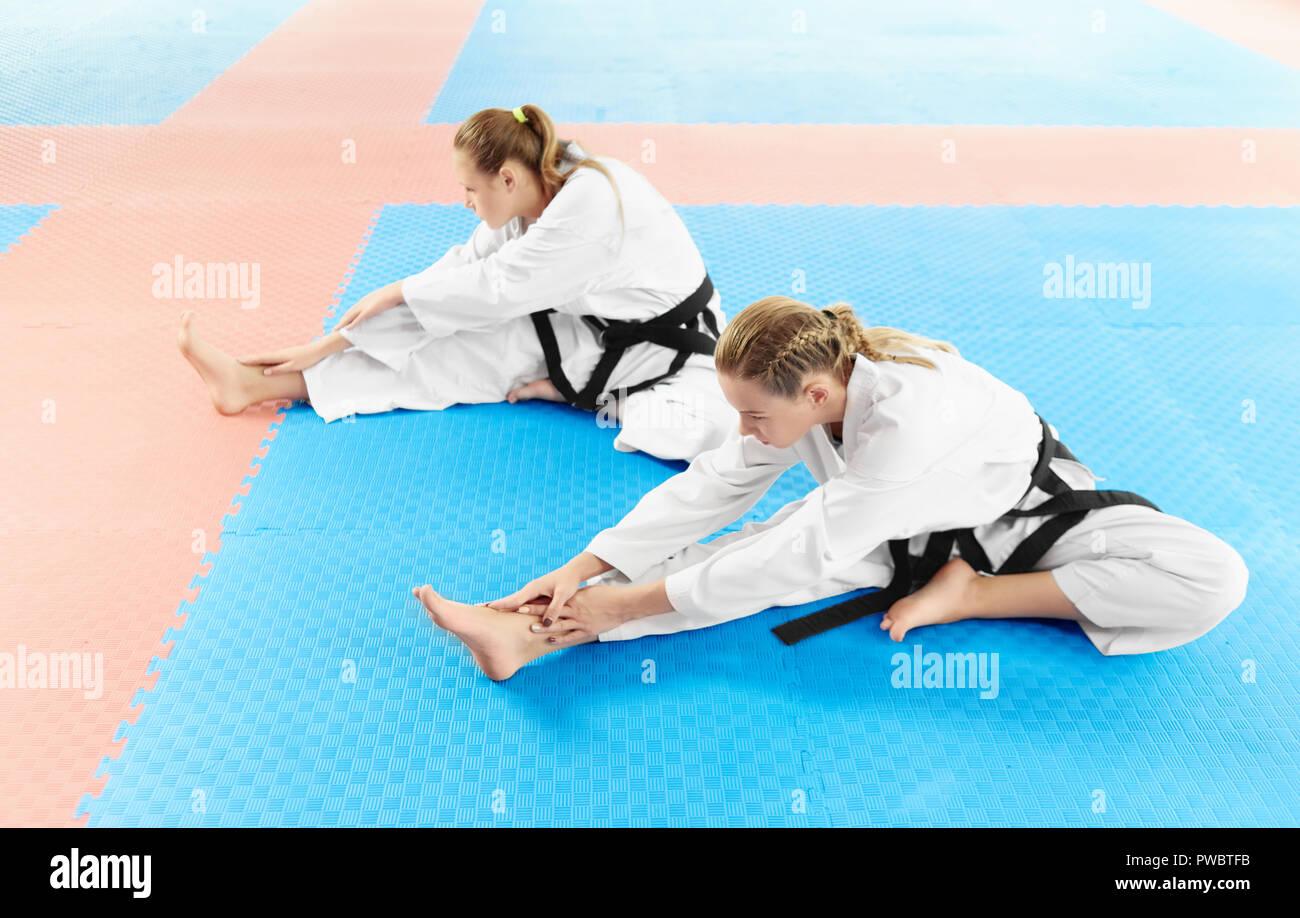 Dos vestida de blanco kimono y cinturones negros, formación su flexibilidad antes del entrenamiento en la lucha de clases. Las hembras jóvenes de karate sentados en el suelo y estirar sus piernas antes de entrenar en el gimnasio de luz. Imagen De Stock