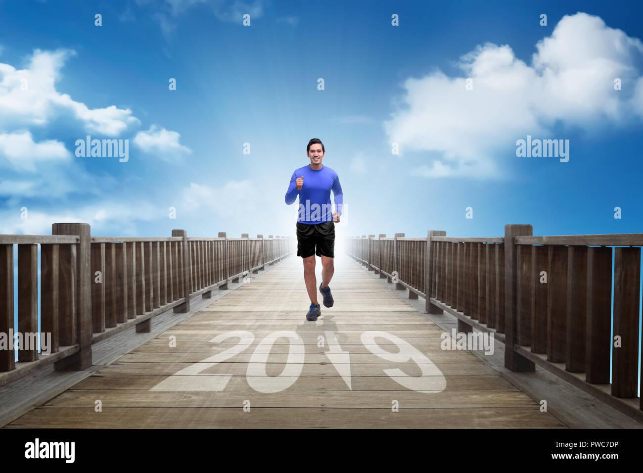 81165ae22bf9 Joven asiático hombre corriendo hacia el año de 2019. Feliz Año ...