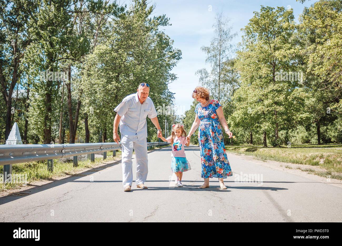 Familia, generación y la gente sonríe feliz concepto - la abuela, abuelo y nieta poco caminando en park Imagen De Stock