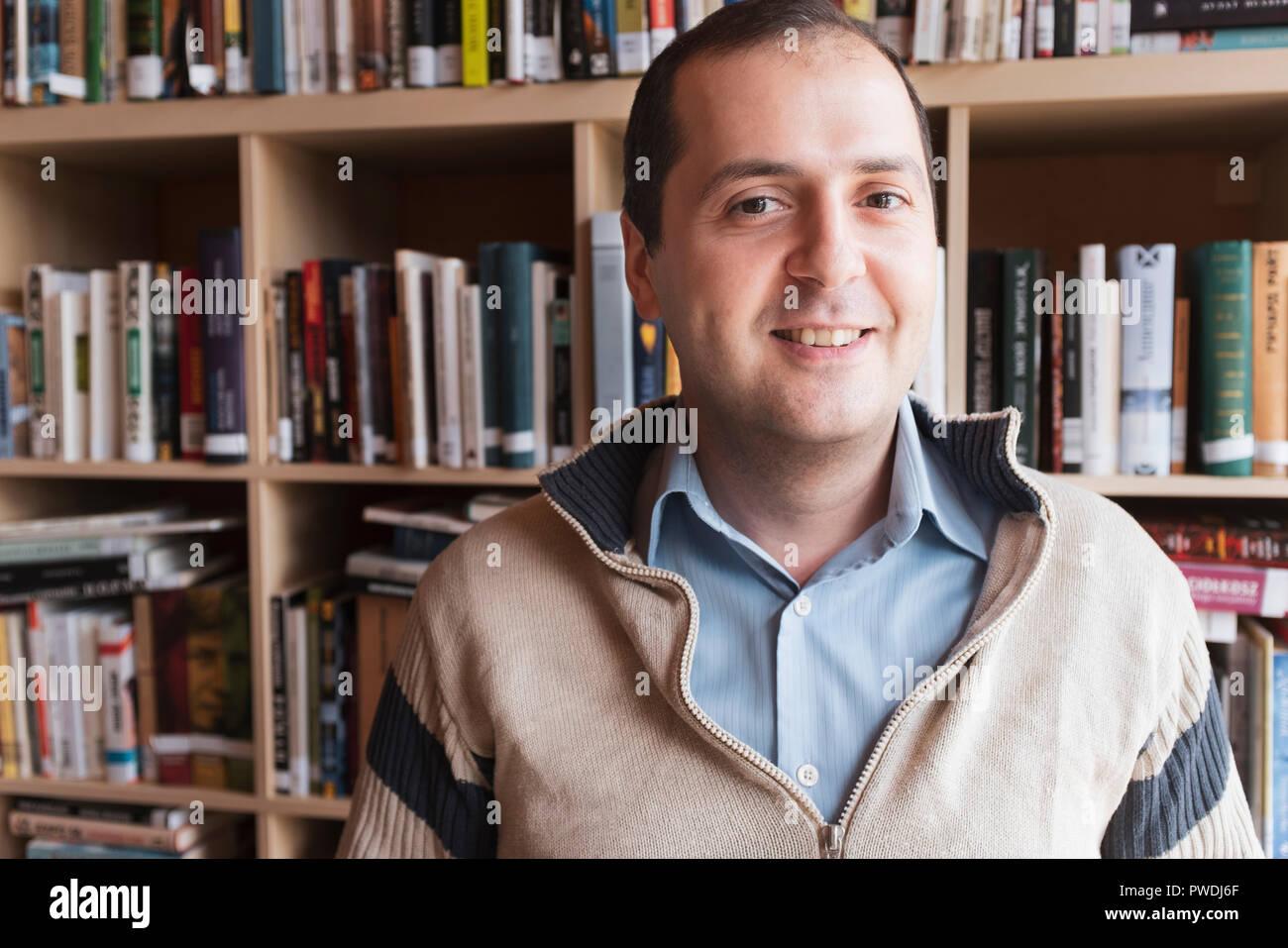 Un hombre sonriente en un puente de una camisa azul en una biblioteca Imagen De Stock
