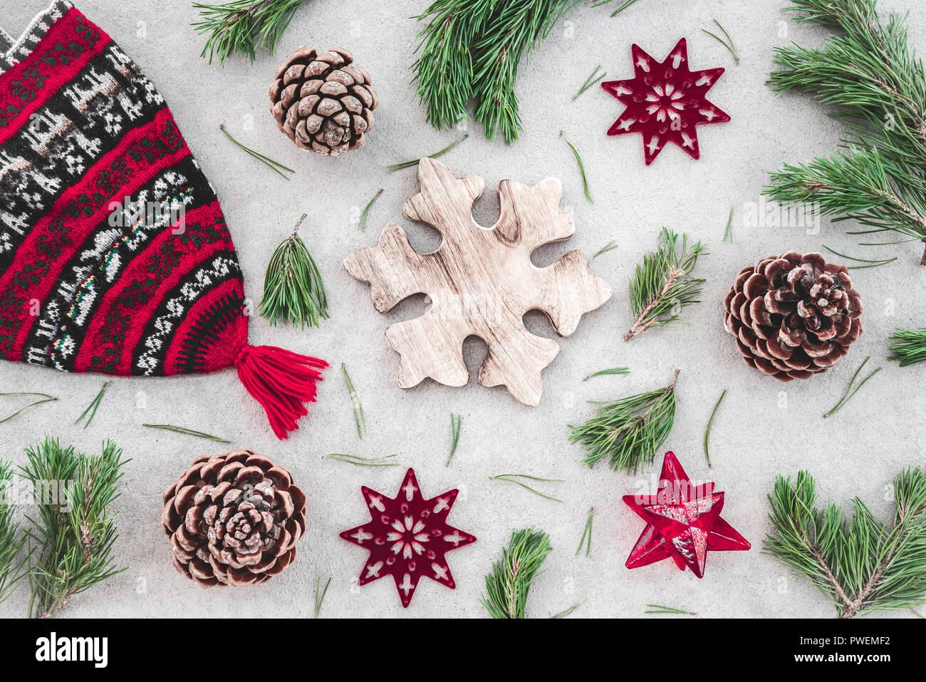 Decoración de Navidad de estilo nórdico. Sombrero de invierno tejido rojo, verde ramas de pino, conos y estrellas, sobre fondo de hormigón. Foto de stock