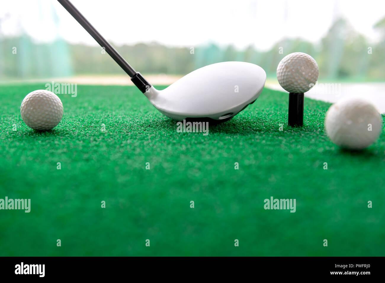 3c453d36b0 Club de golf y pelotas sobre una alfombra de césped sintético en un campo  de entrenamiento