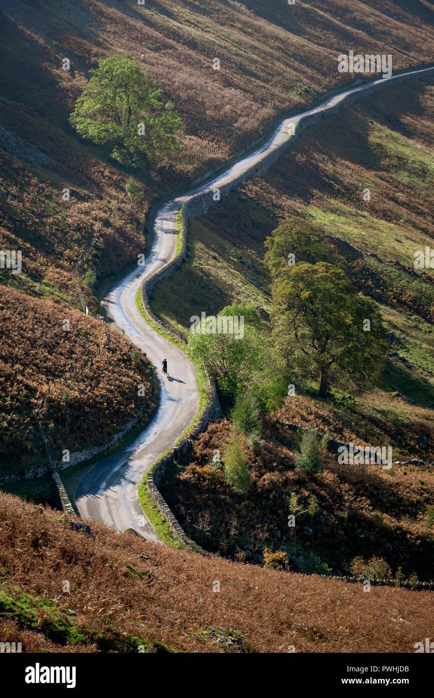 Ciclista solitario en larga y serpenteante carretera a Dudderwick Mardale Haweswater Cumbria Lake District Foto de stock