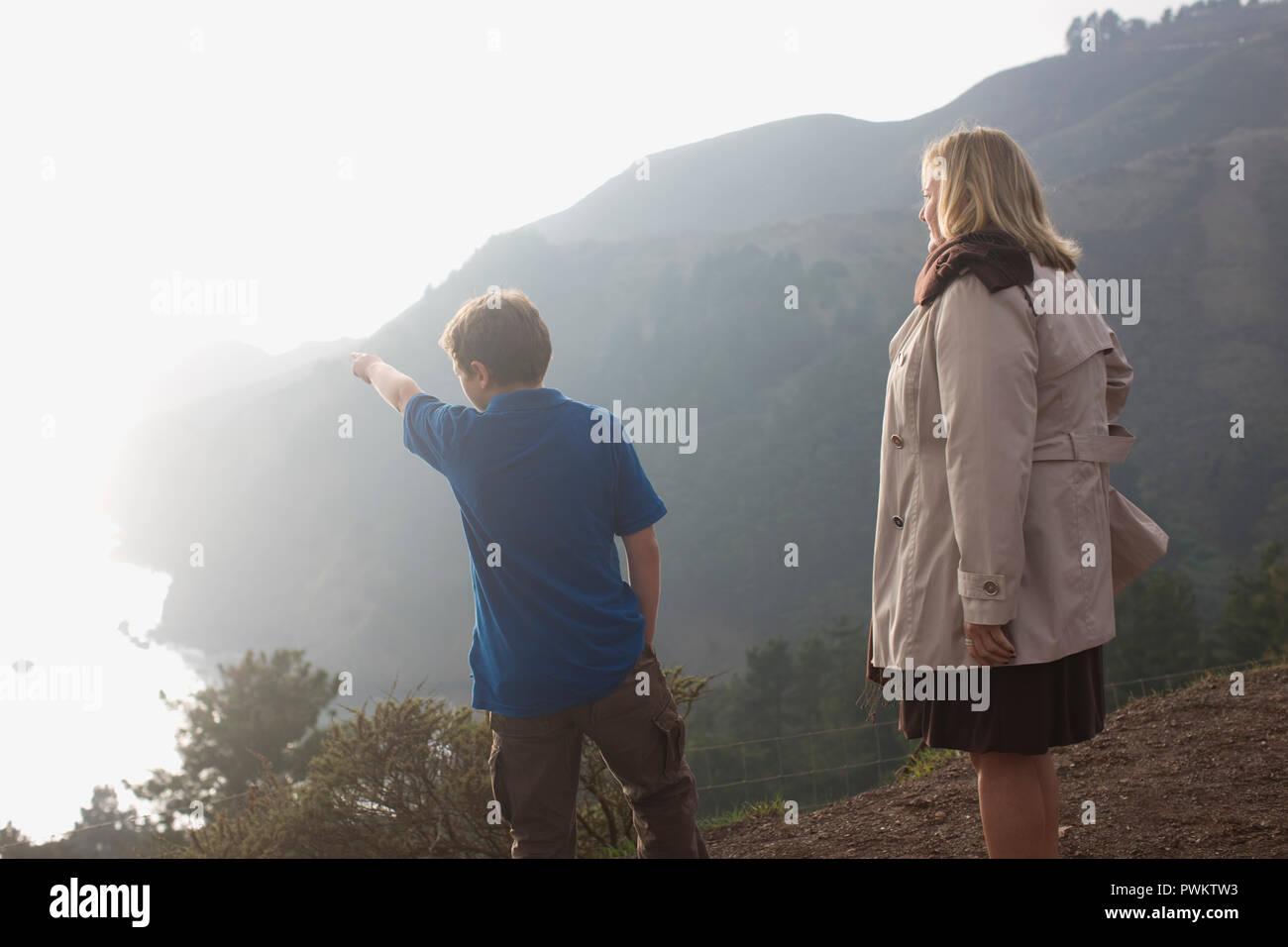 Chico apuntando a algo fuera de la costa mientras está de pie con su madre, al borde de un acantilado. Imagen De Stock