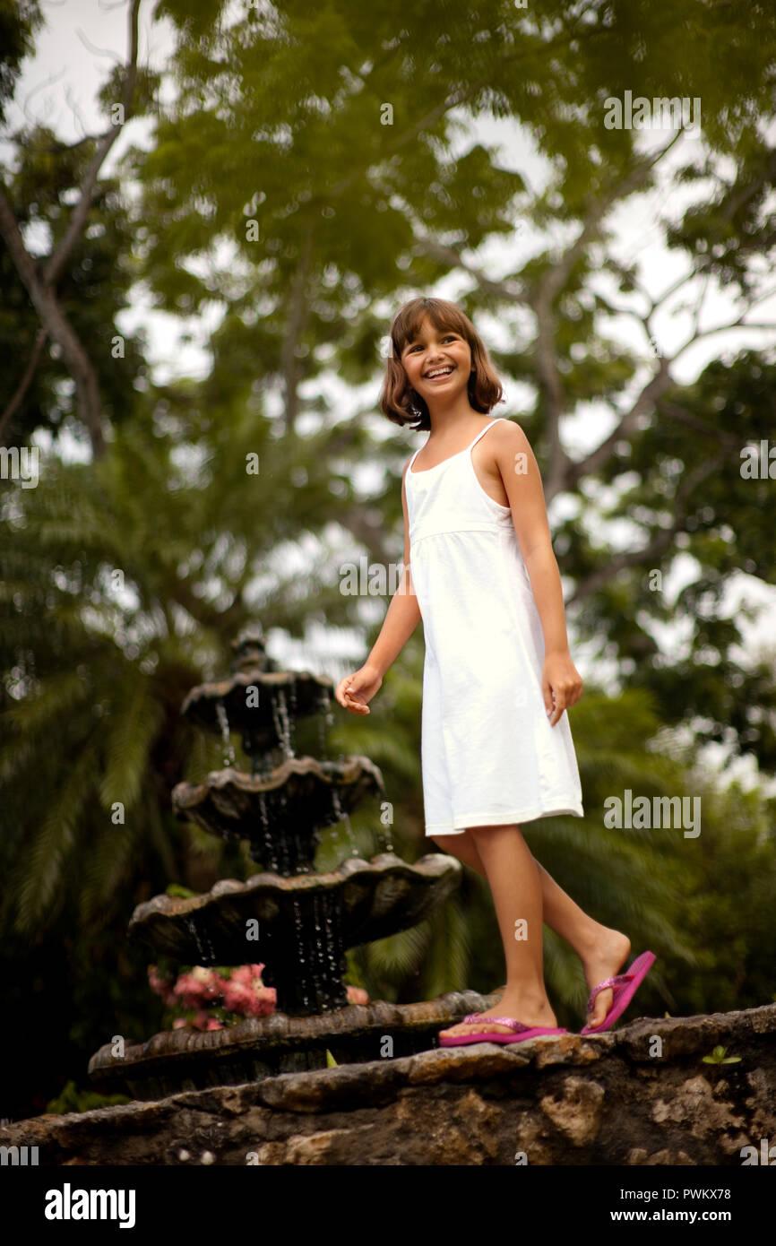 Sonriente joven divirtiéndose equilibrio sobre el muro de piedra de un estanque de jardín. Foto de stock