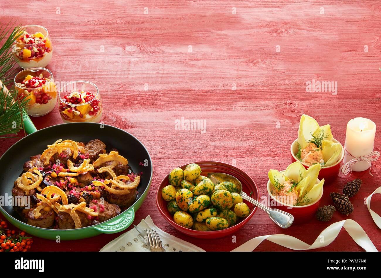 Cena de Navidad con medallones de cerdo, patatas, perejil mousse de salmón y crema de vainilla con una ensalada de naranja y pomelo Foto de stock