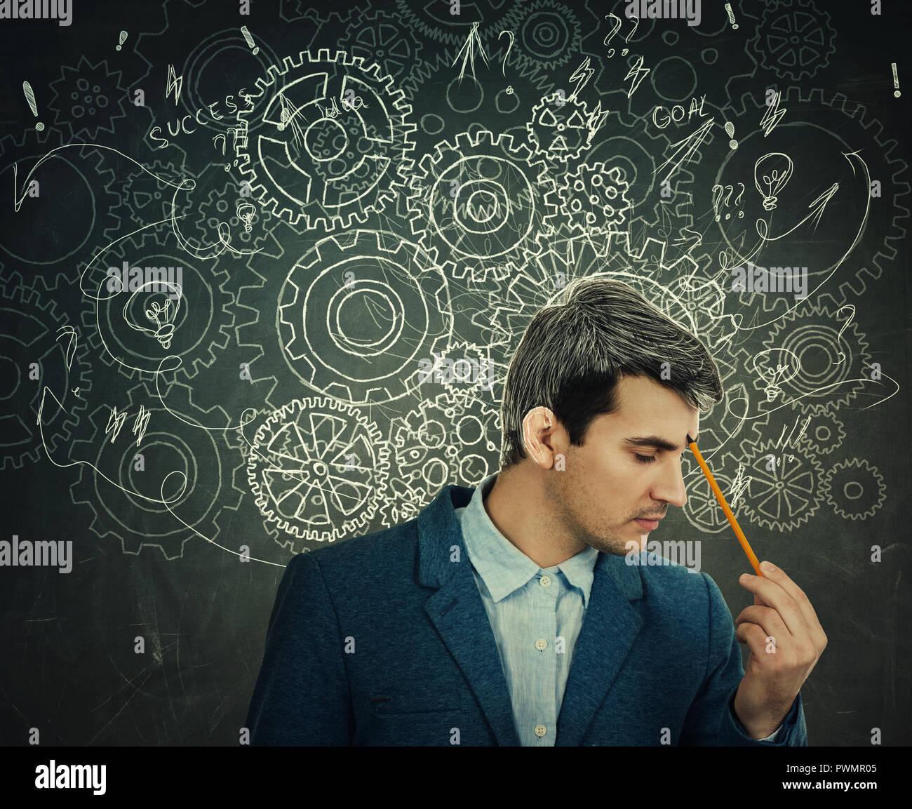 Pensamiento duro seria hombre sobre la pizarra de fondo cerebro engranajes flechas y lío como pensamientos. Concepto de salud mental, su desarrollo psicológico. Imagen De Stock