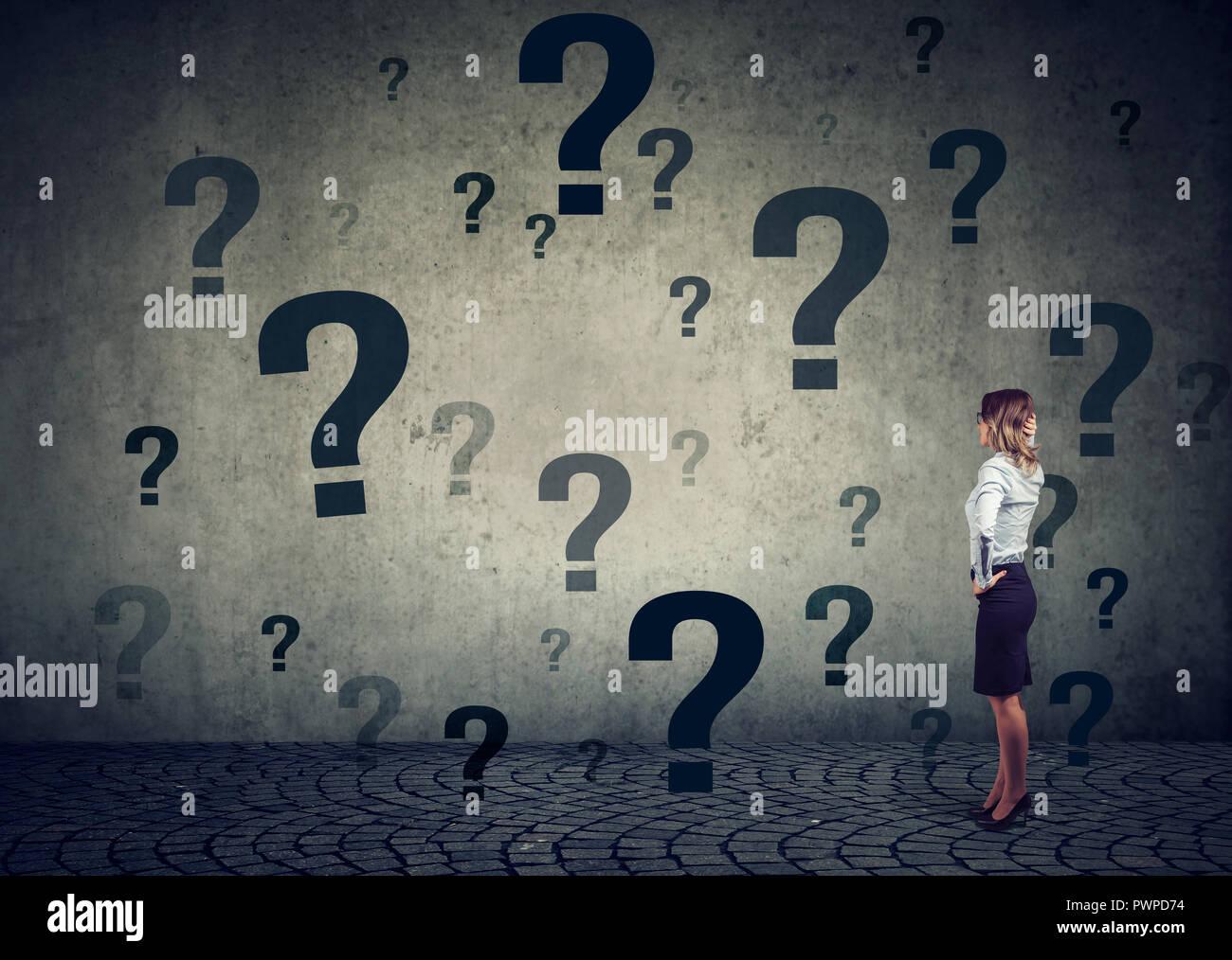 Vista trasera de la joven mujer de negocios con las manos en la cabeza de pie delante de una pared con muchas preguntas preguntando qué hacer a continuación. La empresaria frente a ch Imagen De Stock