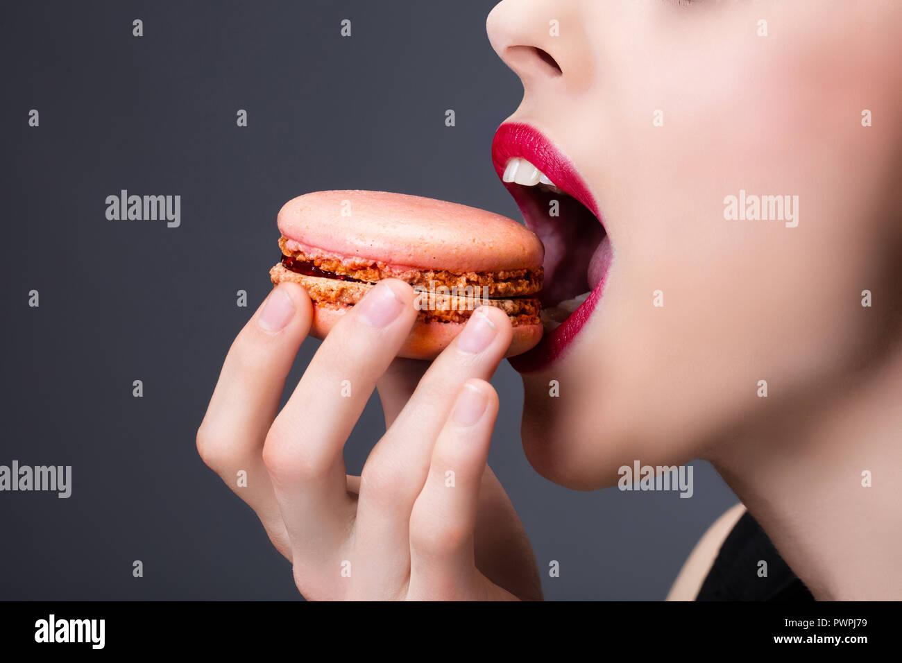 Disparo apretado de una chica disfrutando de un macaroon Imagen De Stock