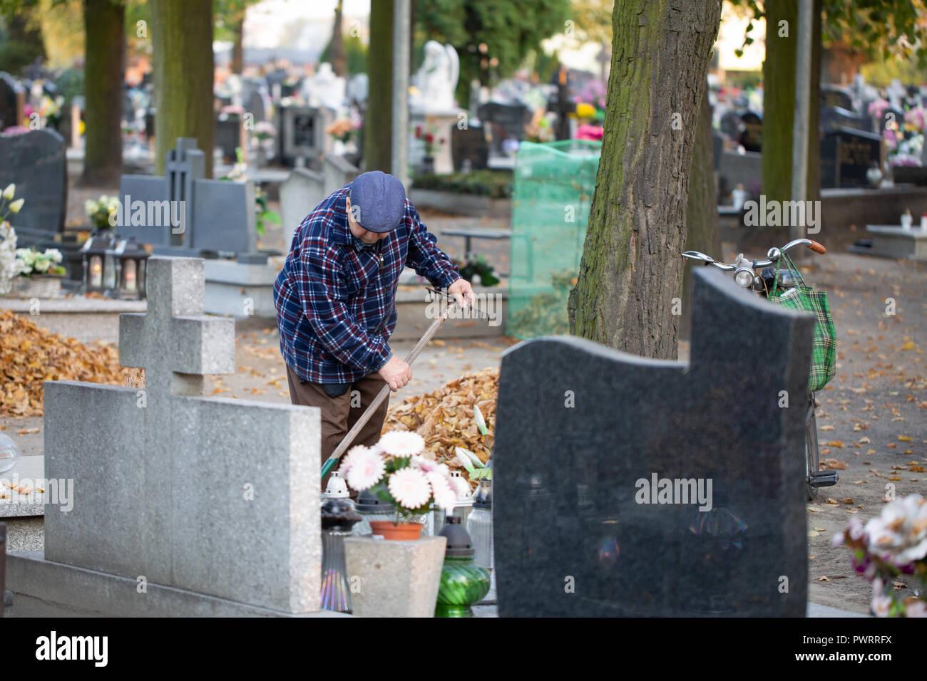 Kostrzyn / Polonia - viejo rastrillar alrededor de una tumba. Cementerio- los preparativos para el Día de Todos Los Santos. Imagen De Stock