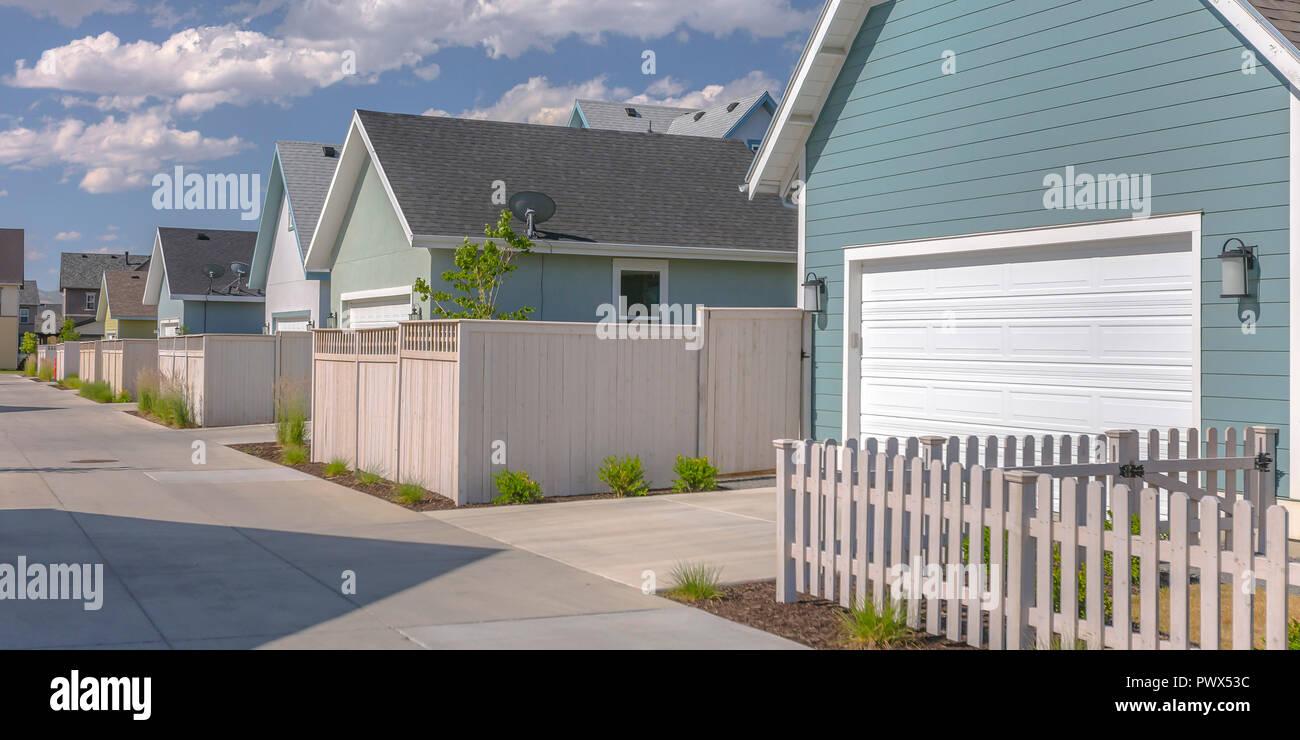 Hilera de casas soleadas con garajes y vallas blancas Imagen De Stock