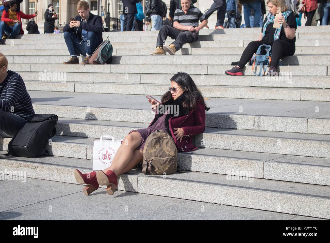 Londres, Reino Unido. El 18 de octubre de 2018. El clima del Reino Unido: una mujer a relajarse en el sol de otoño y caluroso en Trafalgar Square Crédito: amer ghazzal/Alamy Live News Foto de stock