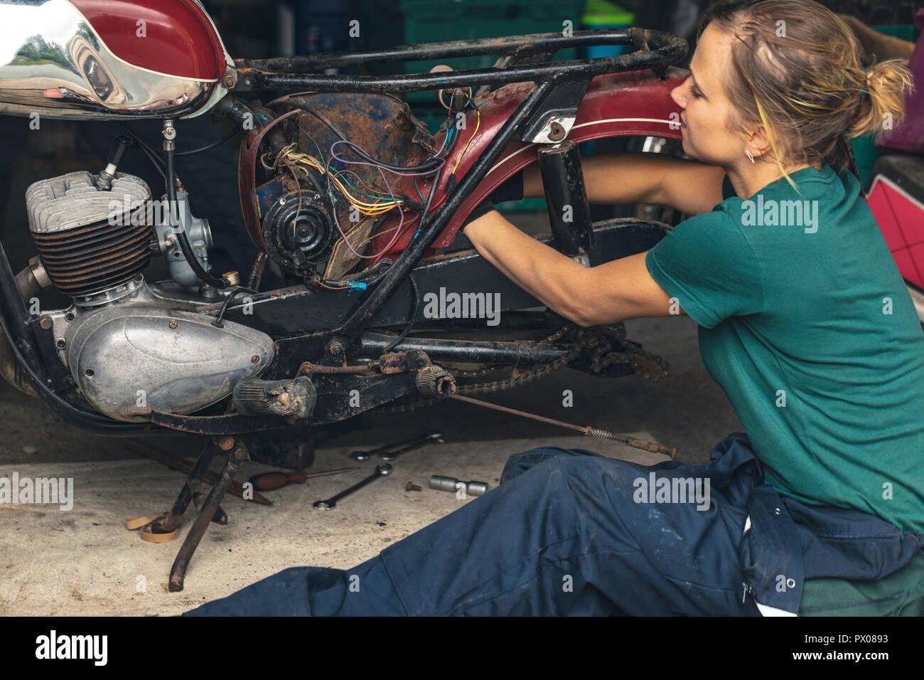 Reparación mecánica femenina moto en garaje Foto de stock