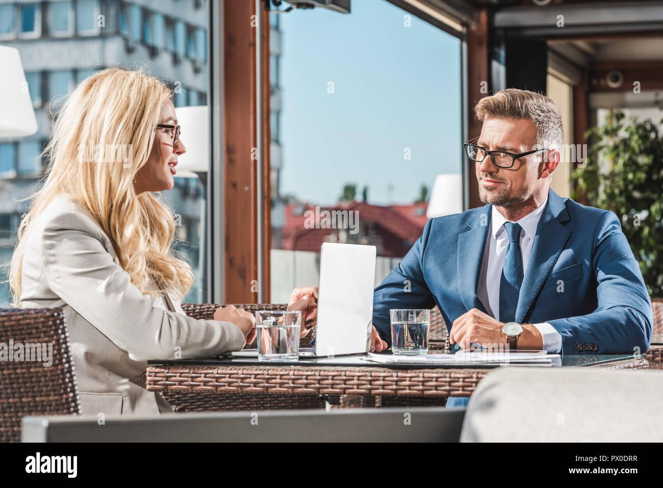 La empresaria con portátil tras reunión con socios comerciales en cafe Imagen De Stock