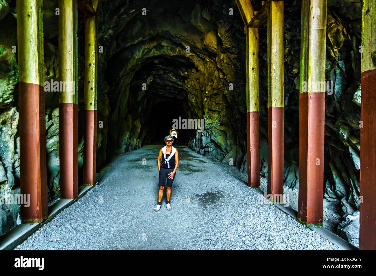 Mujer caminando en el Othello túneles que fueron talladas por la Coquihalla cañón para el ahora abandonado Kettle Valley Railway en esperanza, BC, Canadá Foto de stock
