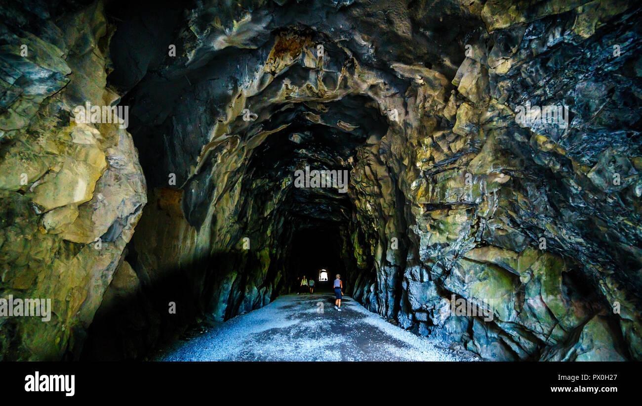 Los turistas que caminan en el Othello túneles que fueron talladas por la Coquihalla cañón para el ahora abandonado Kettle Valley Railway en esperanza, BC, Canadá Foto de stock