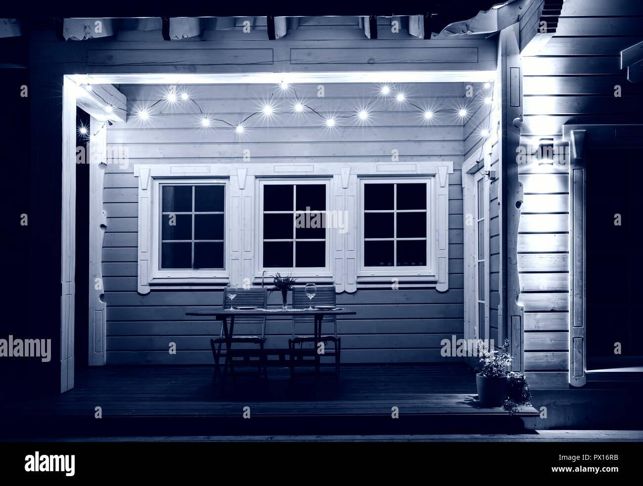 Por La Noche La Terraza De Una Casa De Madera Está