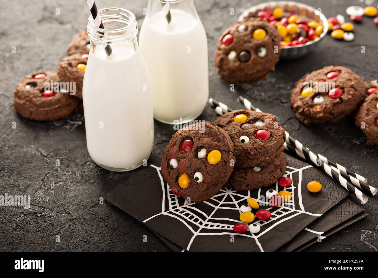Galletas de chocolate con azúcar y dulces ojos con leche para Halloween Imagen De Stock