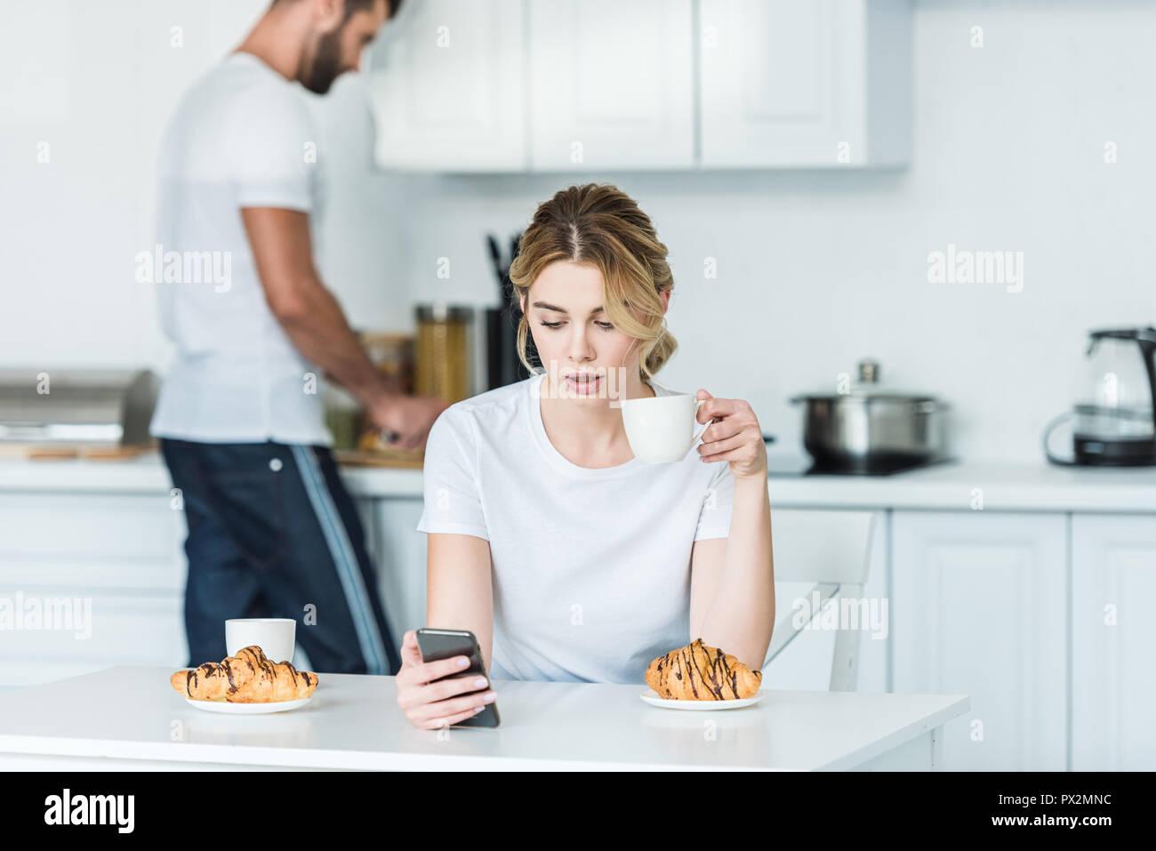 Mujer joven bebiendo café y utilizando el smartphone mientras novio cocinar el desayuno detrás Imagen De Stock