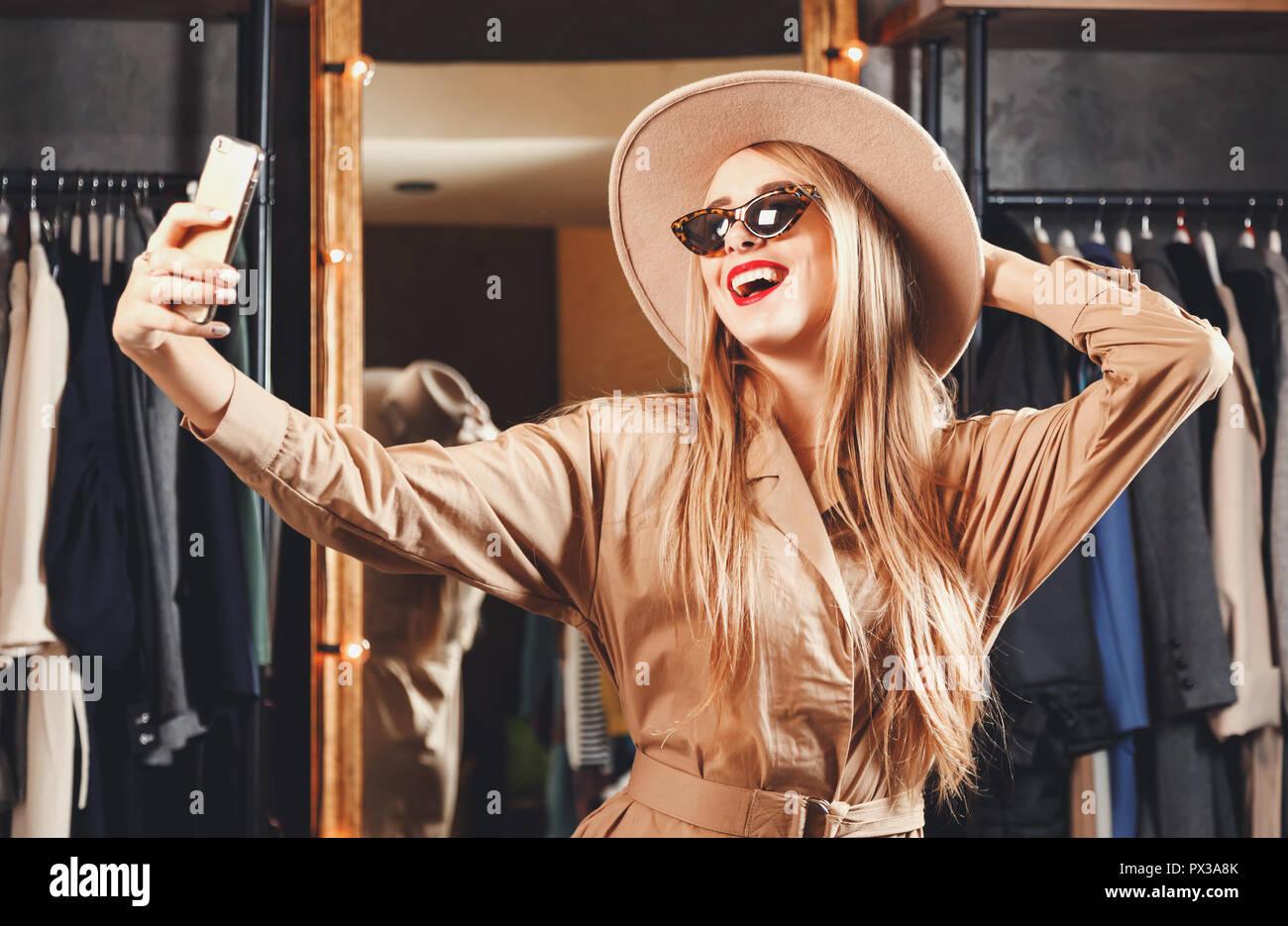 d3ab36605493 Hermosa rubia shopaholic Mujer con gafas de sol y sombrero de moda hacer  selfie en Fashion ...