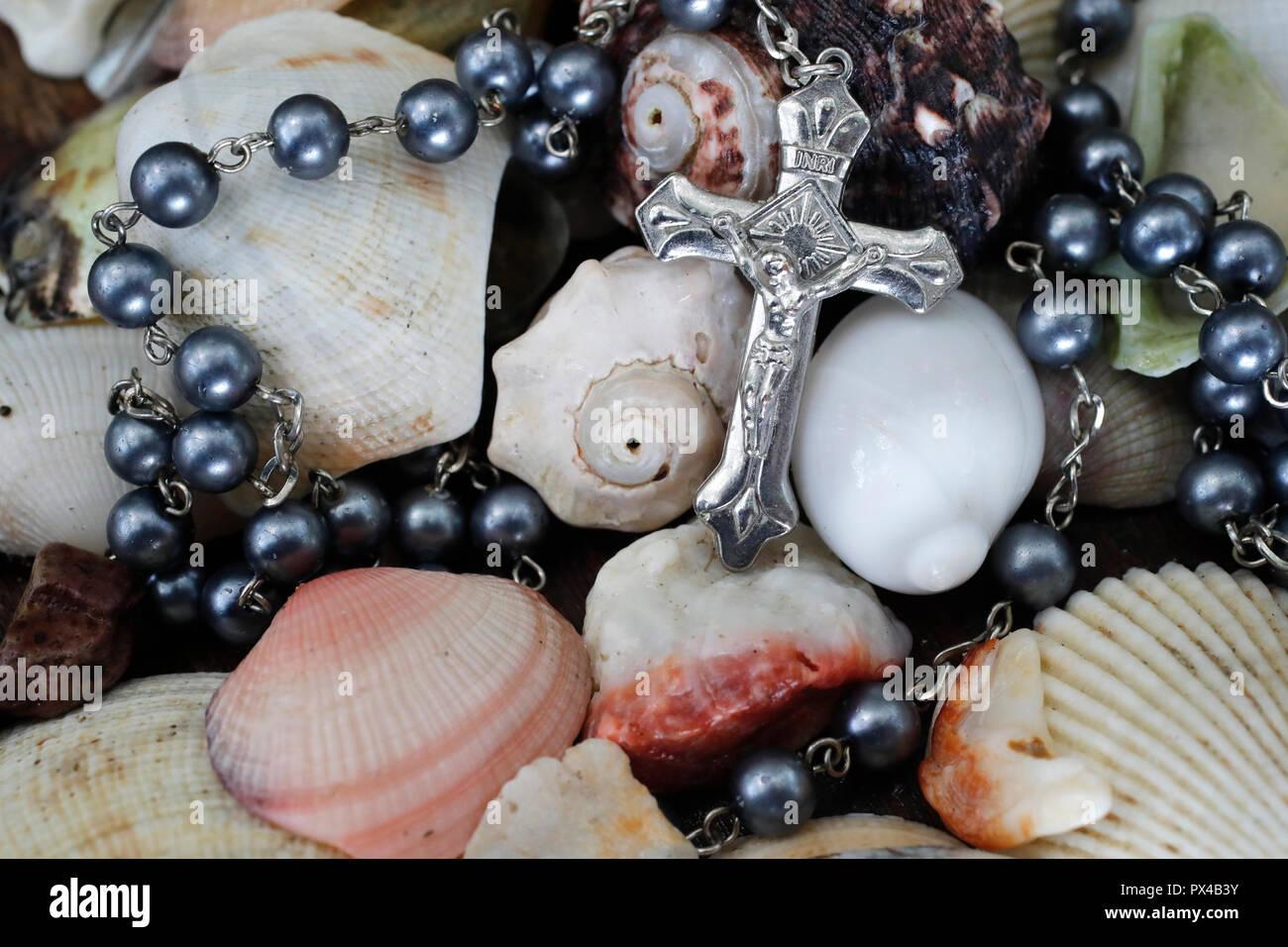 Close-up de cruz con Rosario conchas de mar. Imagen De Stock
