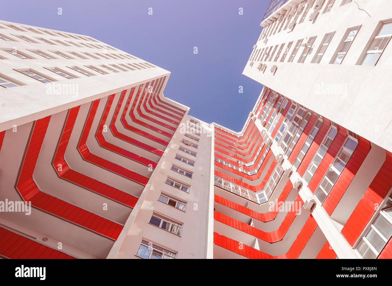 Vista de un edificio residencial de abajo hacia arriba. Casa Blanca con balcones rojo en un cálido día de sol Foto de stock