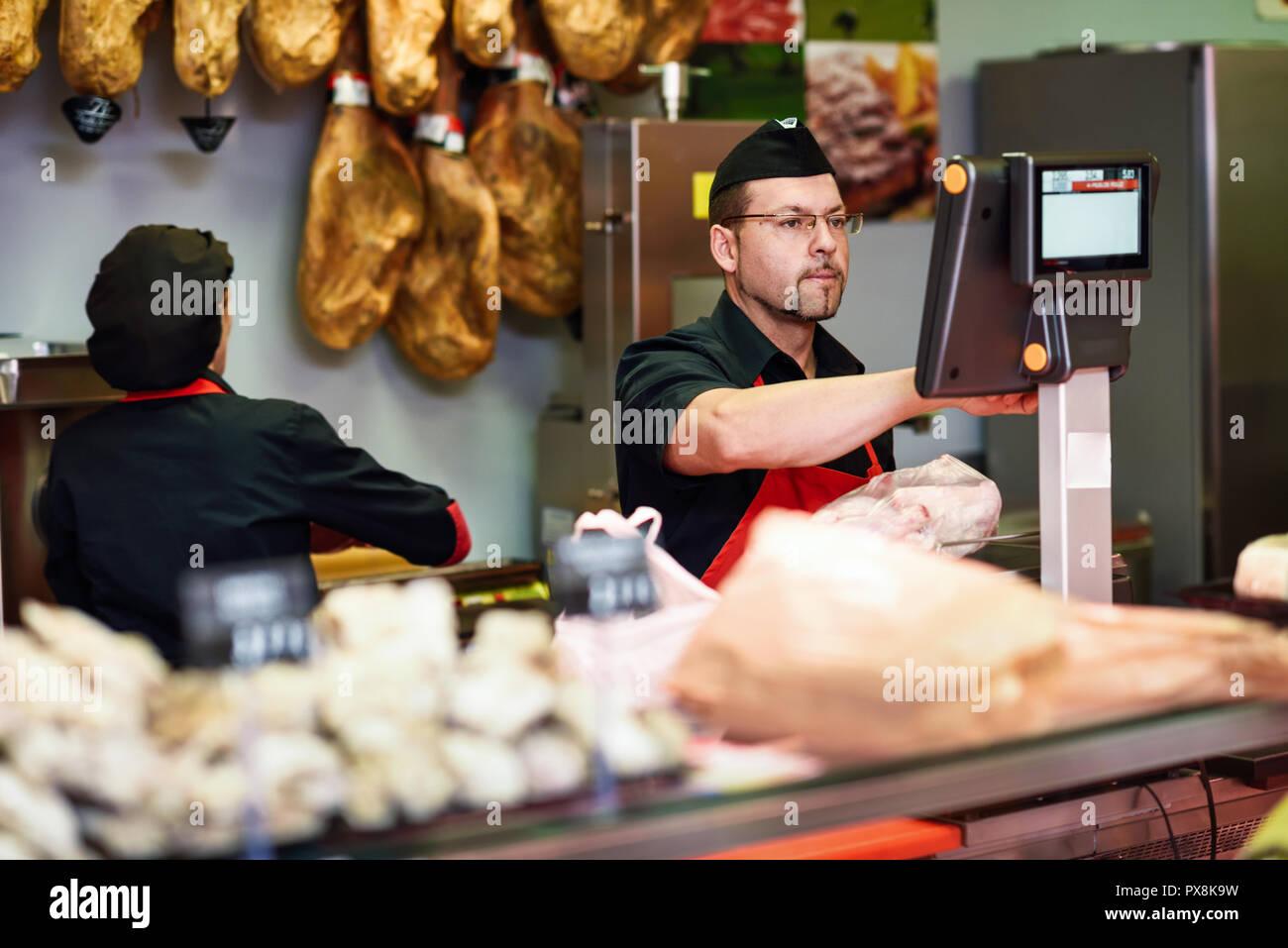 Carnicero en una carnicería pesa la carne y carga con jamón en el fondo Imagen De Stock