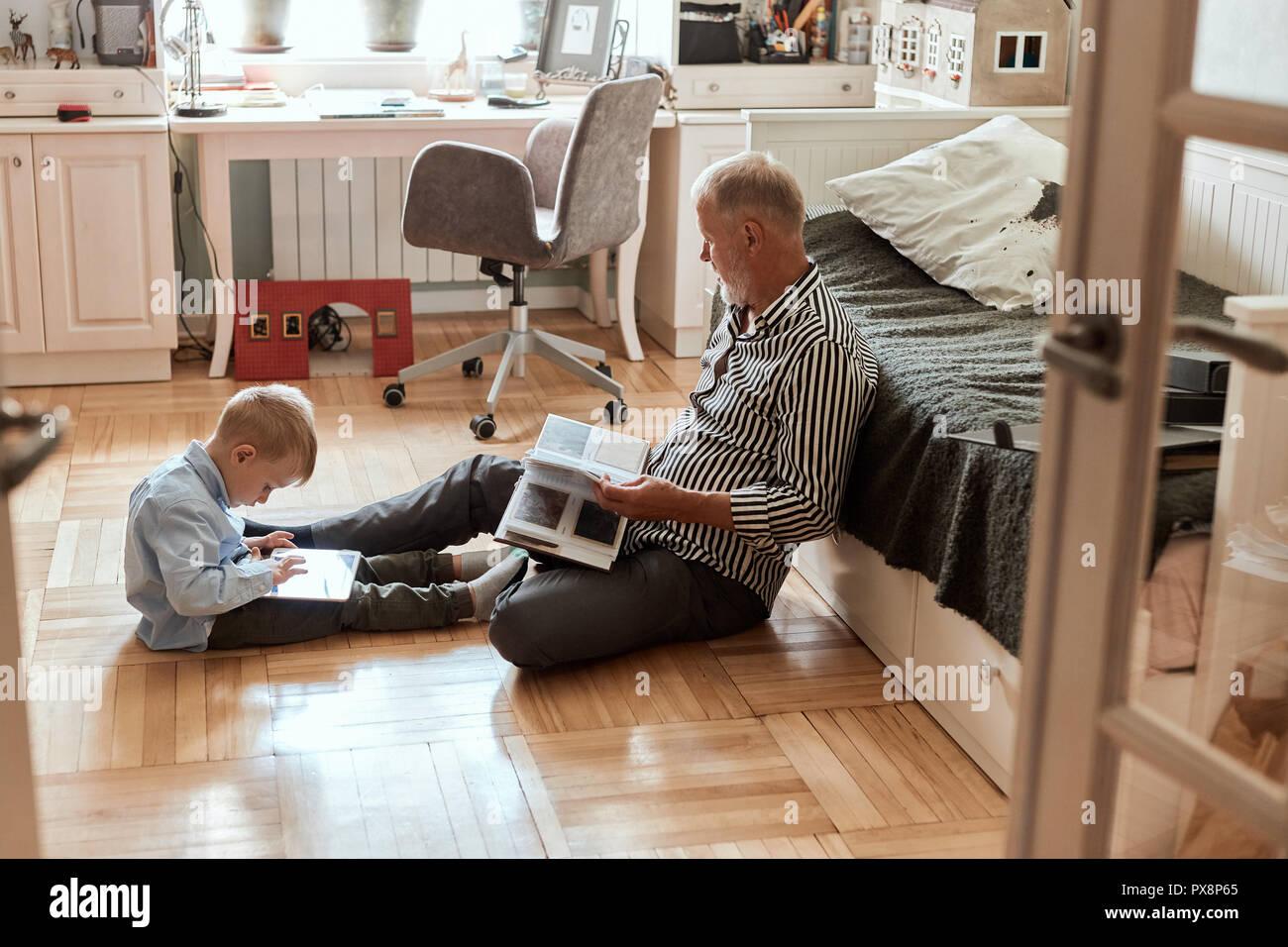 El abuelo mira el álbum de fotos con su boda, Little Boy utilizando tableta electrónica Imagen De Stock