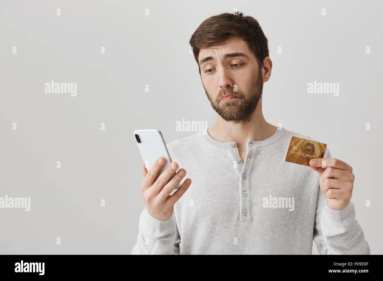 Guy se molesta encontrar no tiene dinero en la cuenta bancaria. Sombrío y triste hombre se ve en la pantalla del smartphone con lástima, mostrando a la cámara de tarjetas de crédito, de pie sobre un fondo gris. Siempre bajo presupuesto mal Imagen De Stock