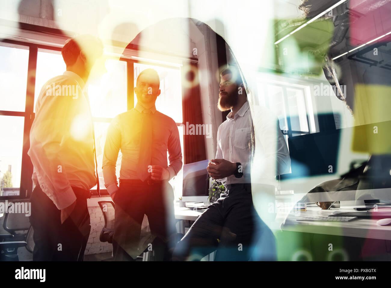 Gente de negocios trabajando juntos en la oficina. Concepto de trabajo en equipo y colaboración. La doble exposición con efectos de luz Imagen De Stock