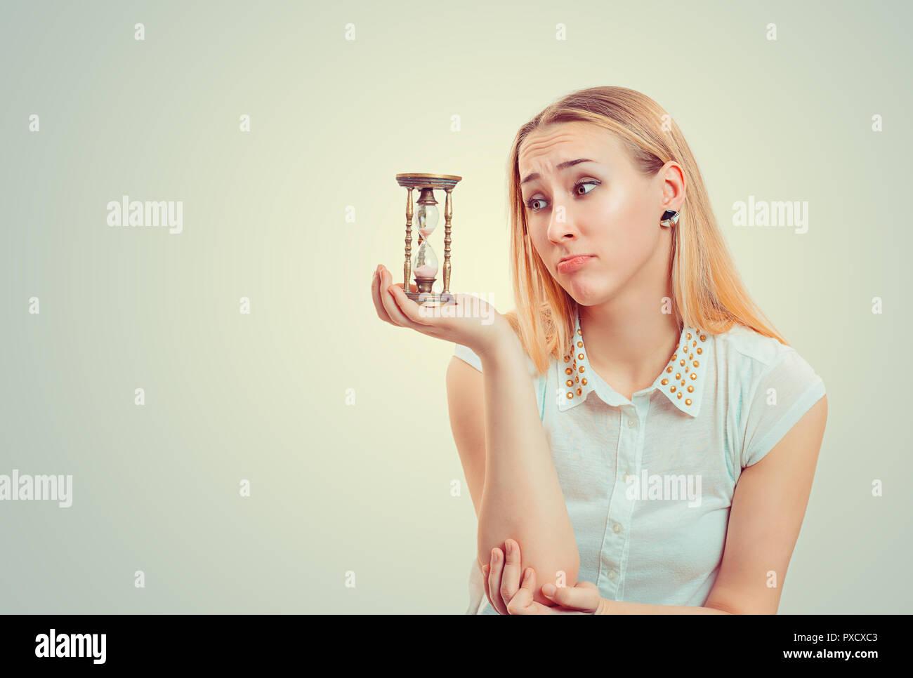 Mujer rubia haciendo lástima expresión facial y mirando el reloj de arena en la esperanza Imagen De Stock