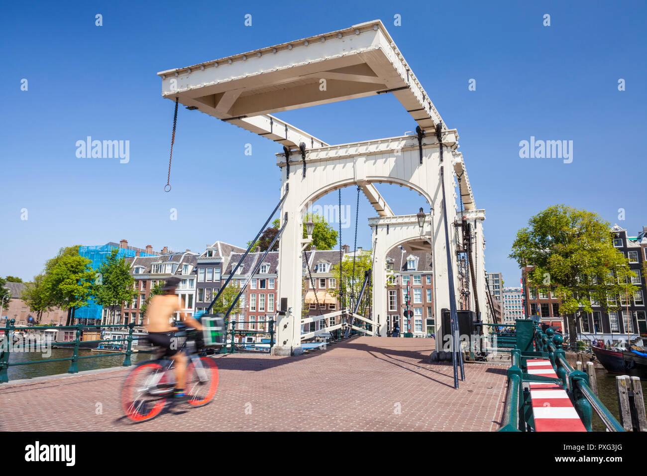 Amsterdam Magere Brug Amsterdam Amsterdam puente Skinny spanning el río Amstel mujer andar en bicicleta Amsterdam Países Bajos Holanda UE Europa Imagen De Stock