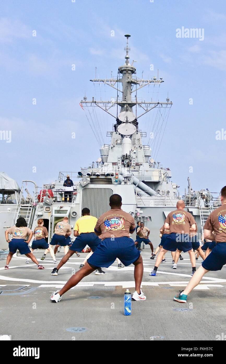 181014-N-N0146-1018 Mar Arábigo (Oct. 14, 2018) marinero 360 participantes participar en un tramo en la cubierta de vuelo antes de empezar el entrenamiento de circuito de misiles guiados a bordo del destructor USS Decatur (DDG 73). Decatur es desplegado en los EE.UU. 5ª Flota de la zona de operaciones en apoyo de las operaciones navales para garantizar la estabilidad y la seguridad marítima en la Región Central, que conecta el Mediterráneo y el Pacífico a través del Océano Índico occidental y tres estratégicos puntos críticos. (Ee.Uu. Navy photo by Ensign Xuan Nguyen /liberado) Imagen De Stock