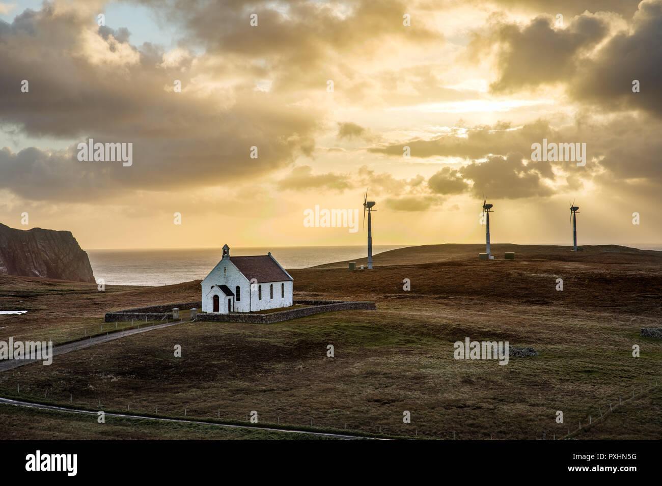 Vista de Fair Isle mostrando la iglesia y las tres nuevas turbinas de viento que proporciona 24 horas de energía eléctrica Foto de stock