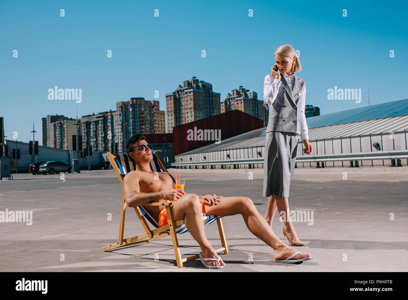 Apuesto joven relajarse en las hamacas mientras que su señora boss en traje junto a él, y hablando por teléfono sobre el estacionamiento Foto de stock