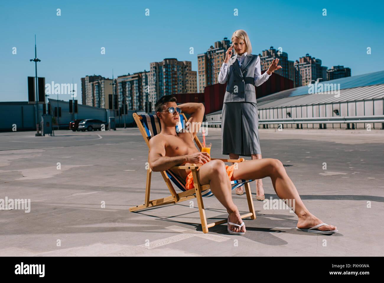 Apuesto joven relajarse en las hamacas mientras su loca lady boss en traje de pie junto a él, y hablando por teléfono sobre el estacionamiento Foto de stock
