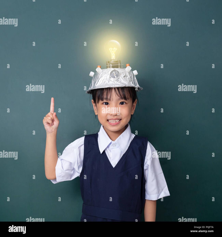 Chino Asia niña llevar casco de realidad virtual y señalando con el dedo hacia arriba para bombilla contra la pizarra verde Foto de stock